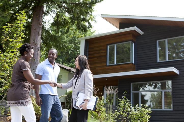 Black couple meets real estate agent outside home.