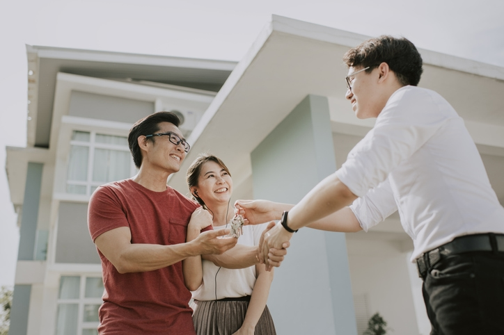 A couple shakes hands with a real estate agent outside a home.