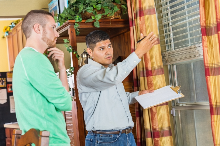 Homeowner and home inspector examine a house's interior window