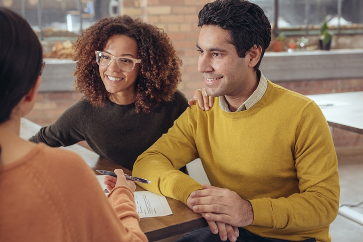 Couple smile while meeting with a loan agent.