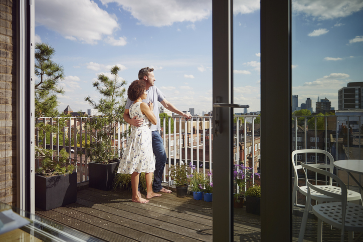 A couple stands on a condo balcony.