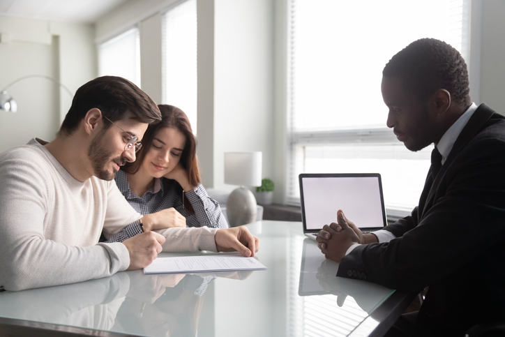 Couple reviewing their house closing costs with a mortgage loan officer