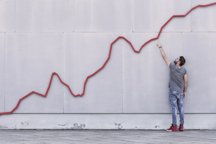 A man stands and points at an ascending red line on a wall.
