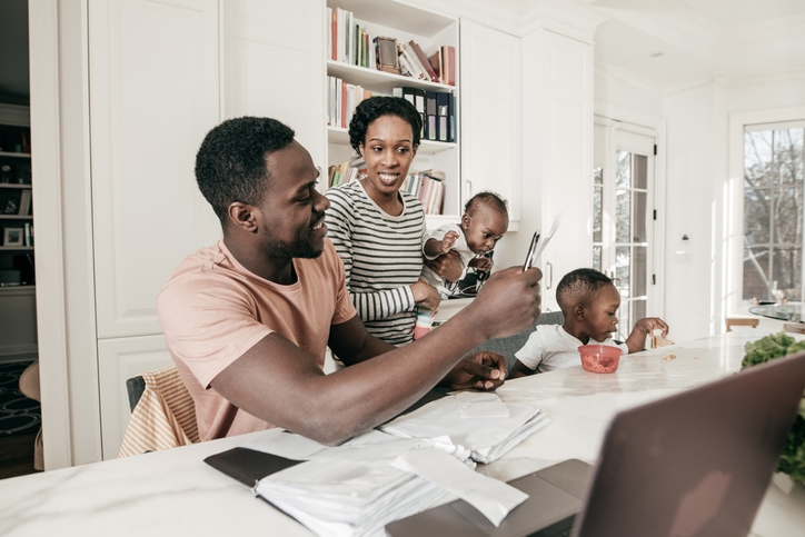 A family reviews finances in the kitchen.
