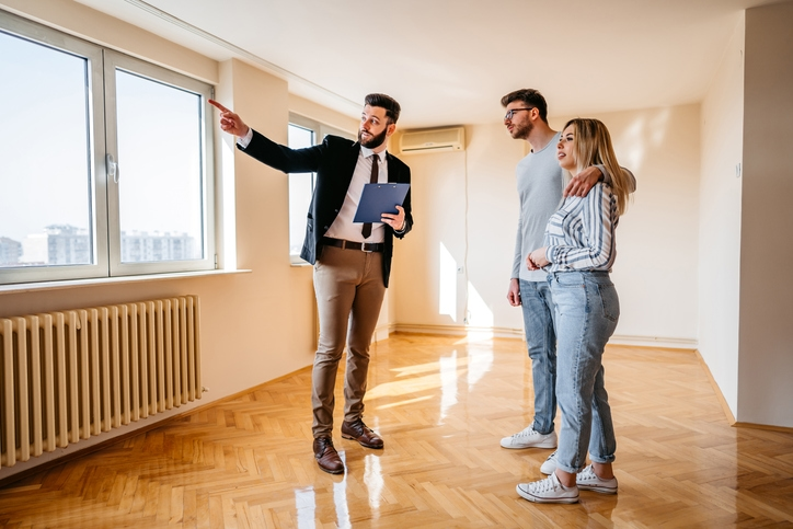 Real estate agent shows couple a condo and explains the house closing process.